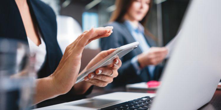 Eine Frau sitzt vor einem Laptop und schaut auf ihr Handy.