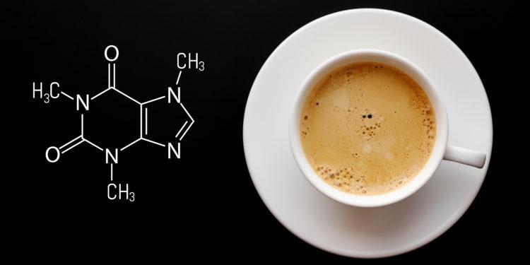 Neben einer Tasse Kaffee steht die chemische Formel für Koffein geschrieben.