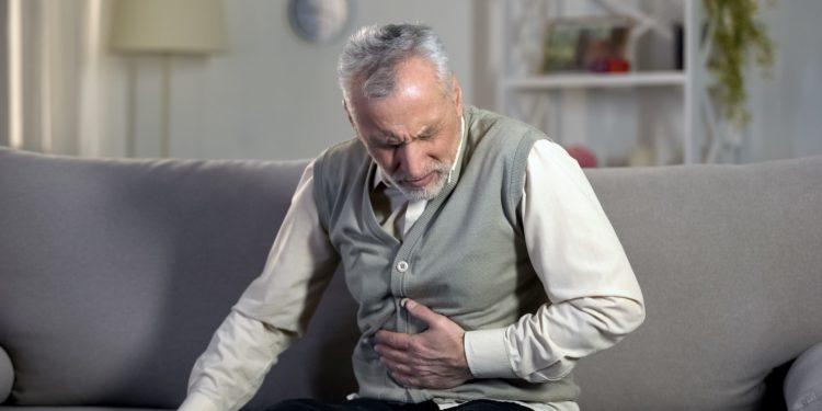 Ein älterer Mann mit schmerzverzerrtem Gesicht sitzt auf dem Sofa und hält sich die Hand an den Bauch.