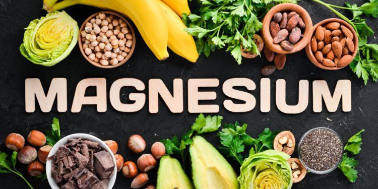 Verschiedene magnesiumreiche Lebensmittel um den Schriftzug Magnesium vor schwarzem Hintergrund
