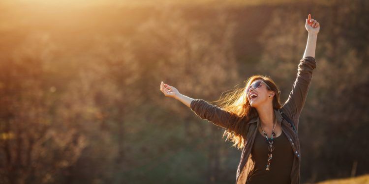 Junge Frau in einer Naturlandschaft lächelt und streckt ihre Arme in die Höhe