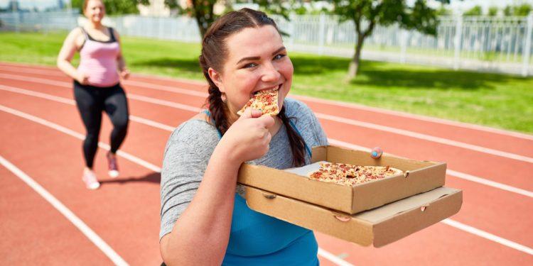 Zwei Frauen joggen über eine Laufstrecke und essen dabei Pizza.