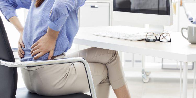 Am Schreibtisch sitzende Frau fasst sich mit ihren Händen an den schmerzenden Rücken