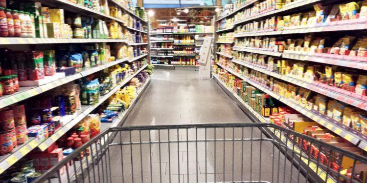 Einkaufswagen zwischen Supermarktregalen