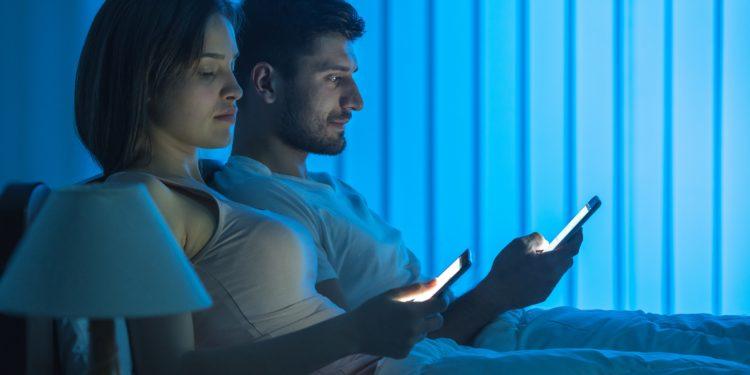Frau und Mann sitzen nebeneinander im Bett und schauen auf ihre Smartphones