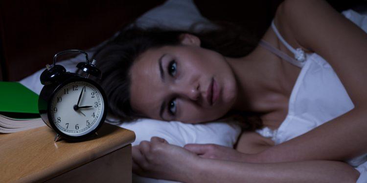 Frau liegt mitten in der Nacht wach im Bett und starrt auf den Wecker