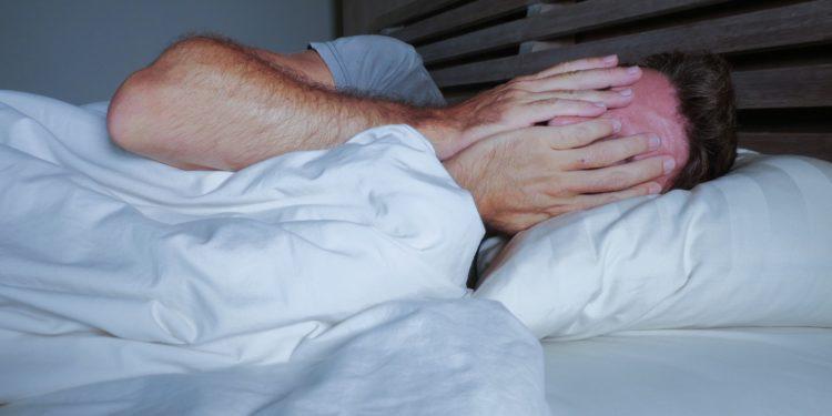 Im Bett liegender junger Mann bedeckt mit seinen Händen sein Gesicht
