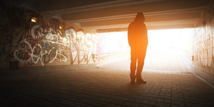 Ein Mann steht in einem mit Graffiti besprühten Tunnel.