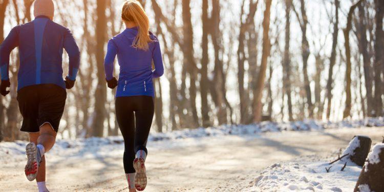Eine Frau und ein Mann joggen in winterlicher Natur