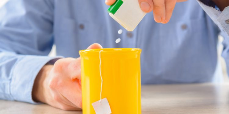 Mann gibt Süßstoff in seine Teetasse