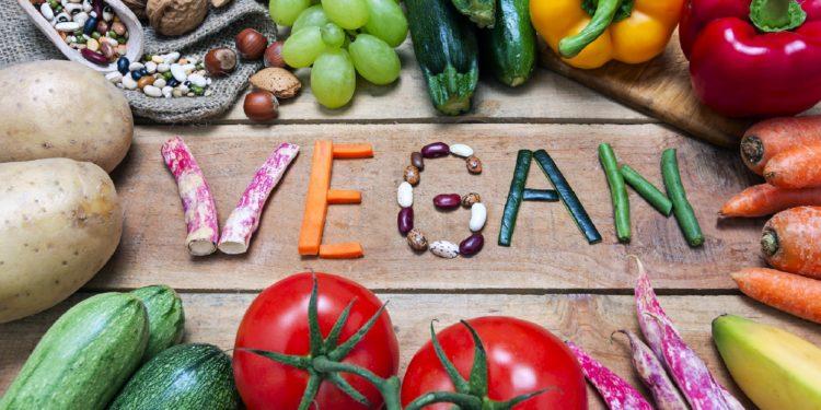 Obst, Gemüse, Nüsse und Hülsenfrüchte um den Schriftzug Vegan auf einem Holztisch