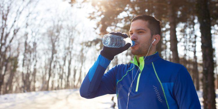 Junger Sportler trinkt Wasser in winterlicher Landschaft