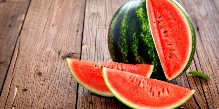 Eine Wassermelone mit zwei herausgeschnittenen Teilen auf einem Holztisch