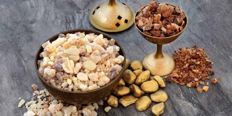 Goldgefärbte Steine, Weihrauch und Myrrhe auf einer Steinplatte