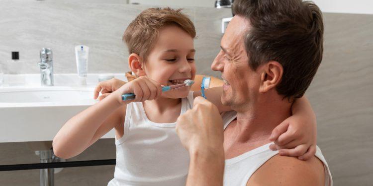 Vater und Sohn putzen gemeinsam Zähne.