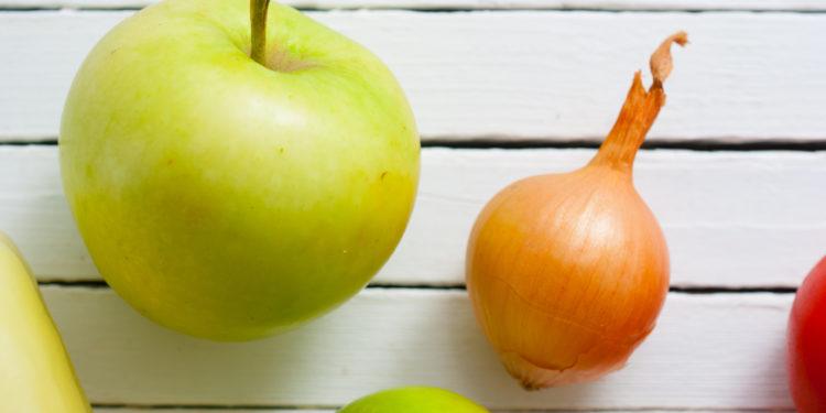 Ein Apfel und eine Zwiebel vor einem weißen Hintergrund.