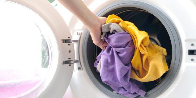 Eine Person füllt bunte Wäsche in die Waschmaschine.