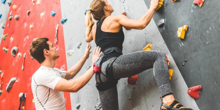 Eine Frau klettert eine Kletterwand in einer Halle hoch.