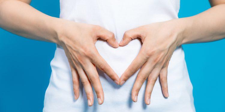 Frau bildet mit ihren Händen ein Herzsymbol vor ihrem Bauch.