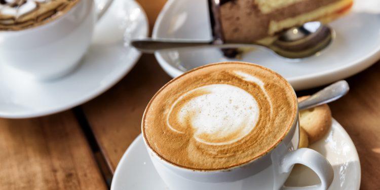 Zwei Tassen Kaffee und ein Stück Torte auf einem Holztisch