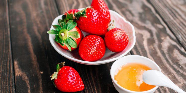 Eine Schale mit Erdbeeren und eine Schale mit Honig auf einem Holztisch
