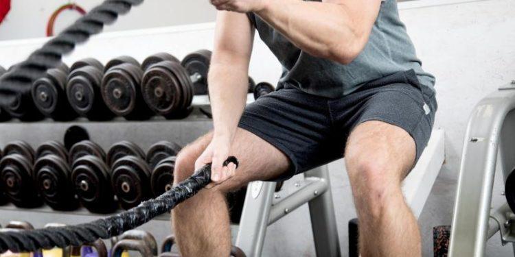 Ein Mann trainiert an Seilen.