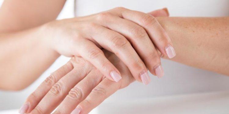 Eine Frau cremt sich die Hände ein.