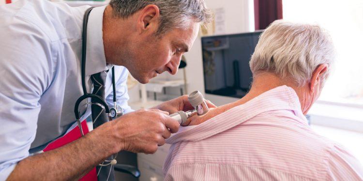 Hautarzt untersucht älteren Patienten auf Anzeichen für Hautkrebs