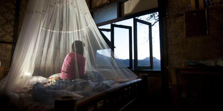 Eine Frau sitzt auf einem Bett, welches von einem Moskitonetz eingehüllt ist.