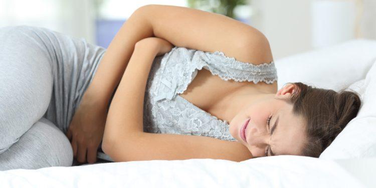 Eine Frau liegt mit schmerzverzerrtem Gesicht und gekrümmter Körperhaltung im Bett und hält sich die verschränkten Arme vor den Unterleib.