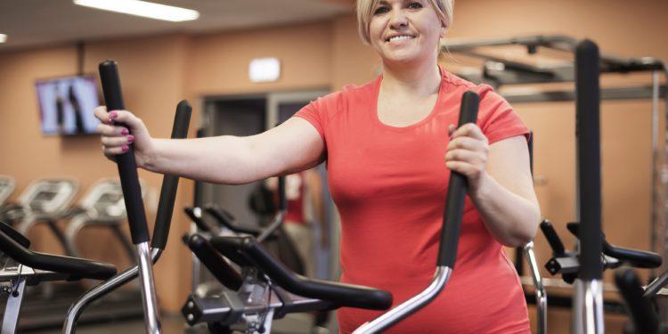 Übergewichtige Frau beim Training im Fitnessstudio