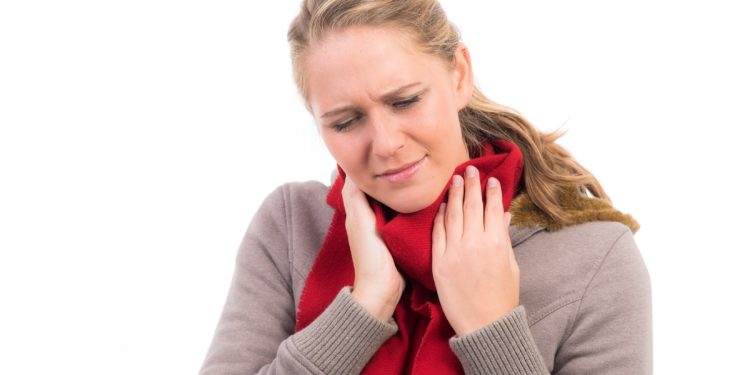 Eine Frau mit schmerzvollem Gesichtsausdruck und umgebundenem Schal hält sich die Hände an den Hals.