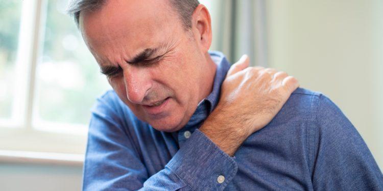 Mann mit schmerzverzerrtem Gesicht fasst sich mit der Hand an die Schulter