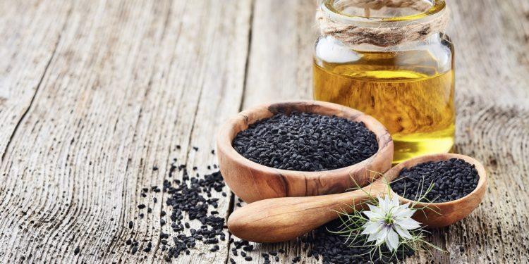 Schwarzkümmelsamen, Schwarzkümmelblüte und Schwarzkümmelöl auf Holztisch