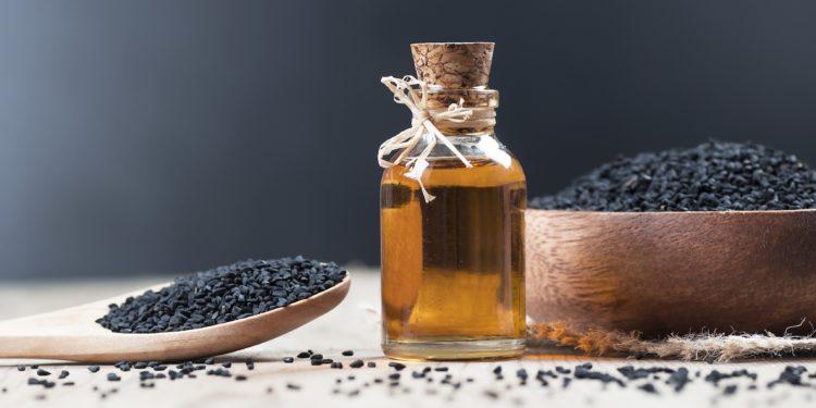 Schwarzkümmelsamen auf einem Holzlöffel und in einer Holzschale sowie ein Fläschchen mit Schwarzkümmelöl in der Mitte.