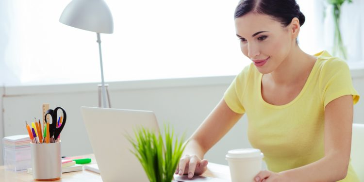 Lächelnde junge Frau sitzt mit einem Kaffee und einer Grünpflanze am Schreibtisch an einem Laptop