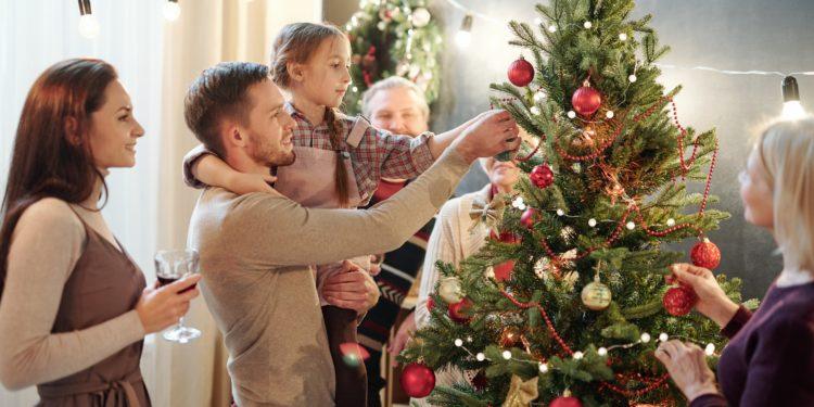 Ein Mann hält ein Mädchen auf dem Arm, welches eine Kugel an einen geschmückten Weihnachtsbaum hängt.