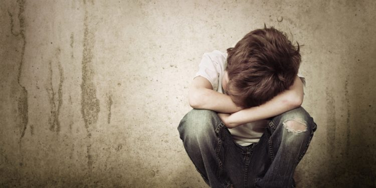Kleiner Junge in der Hocke legt seinen Kopf in seine verschränkten Arme