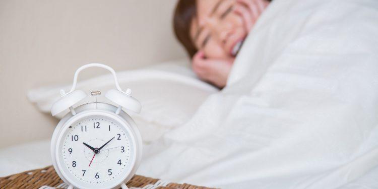 Frau liegt im Bett und hält sich die Ohren zu im Vordergrund steht ein Wecker auf zehn Minuten nach Zehn