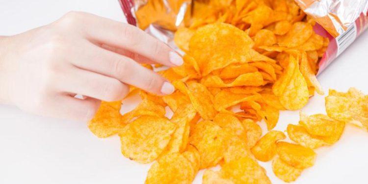 Eine Hand greift in eine Chipstüte.
