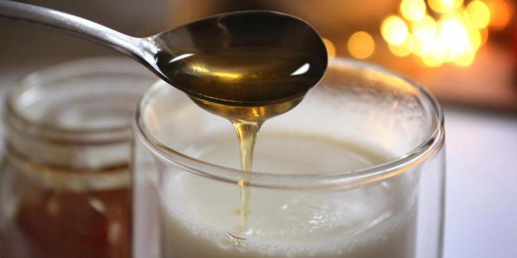 Honig fließt von einem Löffel in ein Glas mit heisser Milch.