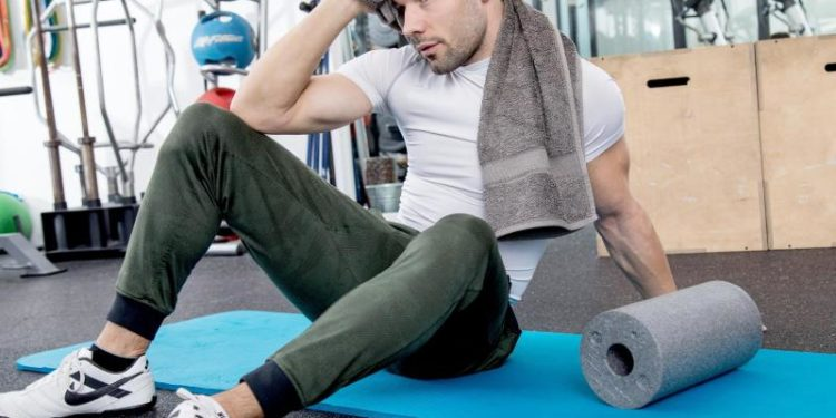Ein Mann wischt sich den Schweiß mit einem Handtuch ab.