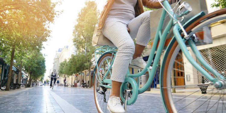 Ältere Frau fährt in der Stadt mit dem Fahrrad
