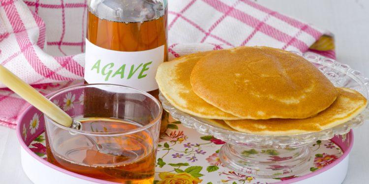 Auf einem Tablett stehen eine Flasche und ein Glasschälchen mit Agavensirup sowie eine kleine gläserne Kuchenplatte mit mehreren Pancakes.