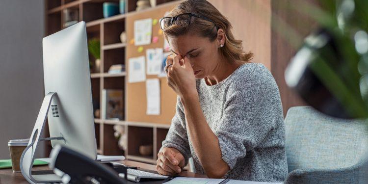 Frau im Büro hat Kopfschmerzen und fasst sich an die Nasenwurzel