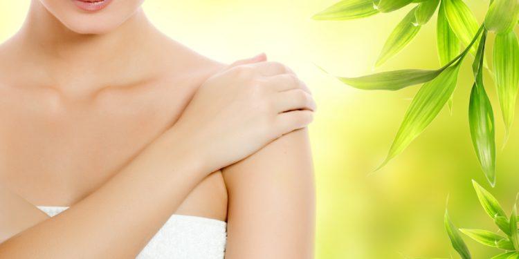 In ein weißes Handtuch gewickelte Frau legt die rechte Hand auf die linke Schulter, im Hintergrund sieht man Sonnenlicht und grüne Blätter