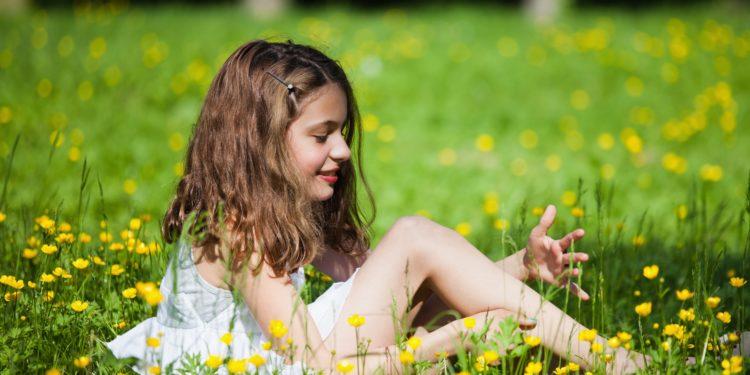 Ein Mädchen sitzt auf einer Sommerwiese inmitten vieler Butterblumen.