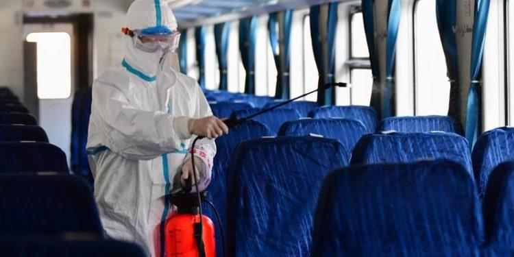 Eine Person in einem Schutzanzug desinfiziert ein Zugabteil.