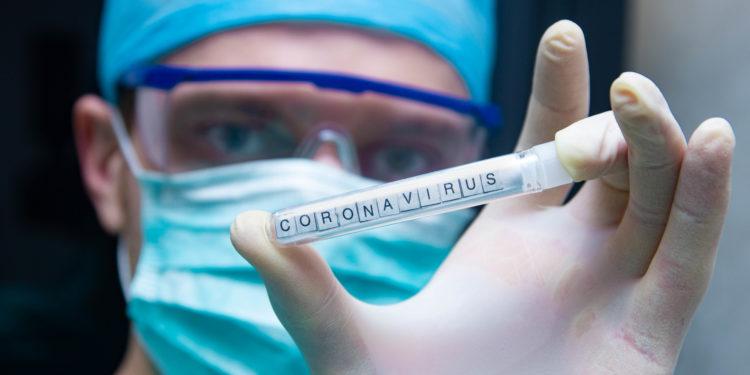 Ein Wissenschaftler hält ein Reagenzglas mit der Aufschrift Coronavirus in der Hand