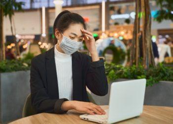 Eine Frau sitzt mit einem Mundschutz vor einem Notebook.